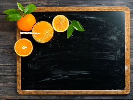 Glass of orange squeezed juice and orange fruits with green leaves on a chalkboard with copy space. Above view.