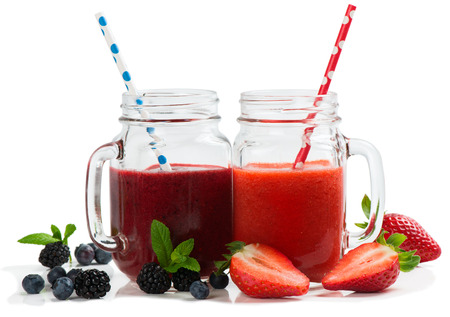 a straw:  Smoothies from summer berries ( strawberry; blueberry and blackberry ) in mason jars with straws isolated on white background.