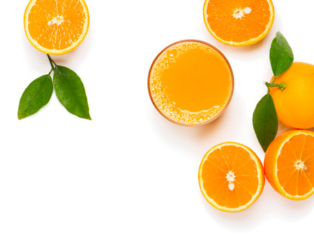 Top view of glass of orange juice and orange fruits with green leaves isolated on white background.