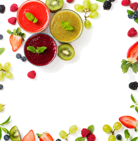 Top view of juices smoothie of summer fruits and berries - strawberry, raspberry, blueberry, blackberry, kiwi and grape isolated on white background.  Frame made from fruits. Stock Photo