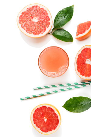 Top view of glass of grapefruit juice and slices of grapefruit fruits with green leaves isolated on white background.
