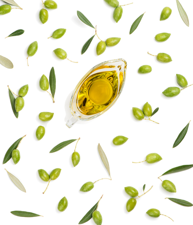 Green olive fruits with leaves and olive oil isolated on white background, top view.