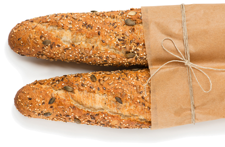 Top view of two baguettes baked bread in paper with different seeds ( pumpkin, poppy, flax, sunflower, sesame, millet ) isolated on white background.