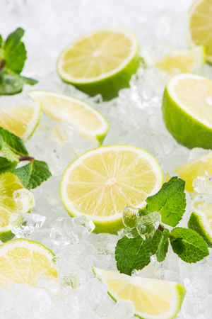 Sliced fresh lime fruits on ice cubes decorated with mint leaves. Selective focus on the mint.
