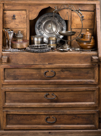Old kitchen utensils on a rustic wooden sideboard.