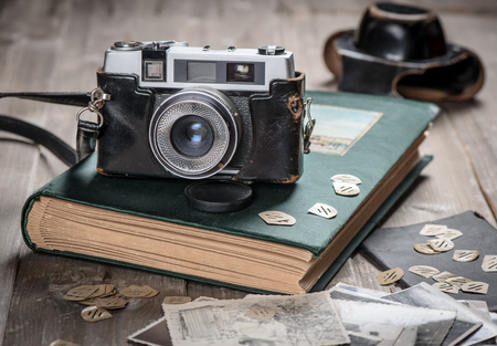 Petro foto album, old photos and camera on wooden table.