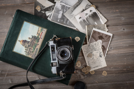 Old retro film camera, foto album and photographs on rustic wooden boards background. above view.