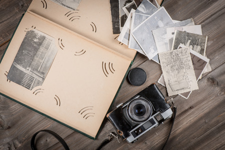 Opened foto album with copy space, vintage photos and camera on wooden background, above view.