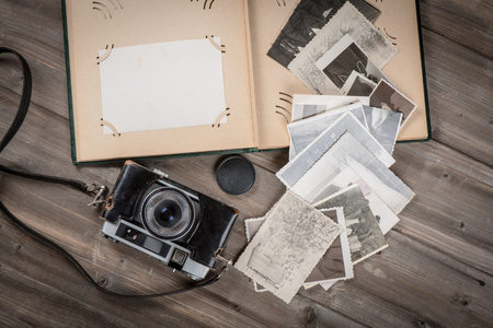 Top view of opened foto album with copy space, old photos and camera on wooden background. above view. Stok Fotoğraf