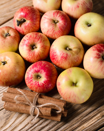 Group of ripe apples with cinnamon over wooden texture