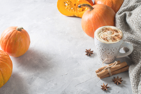 Pumpkins spice latte with pumpkins and leaves over white wood texture. Copy space.