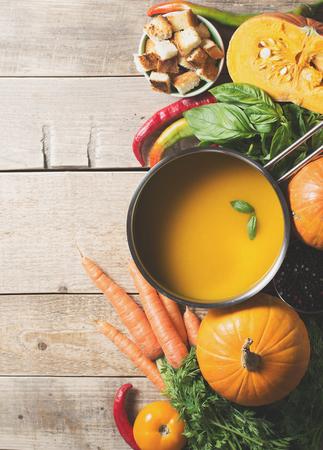 Creamy pumpkins soup with vegetables over black texture. selective focus. copy space