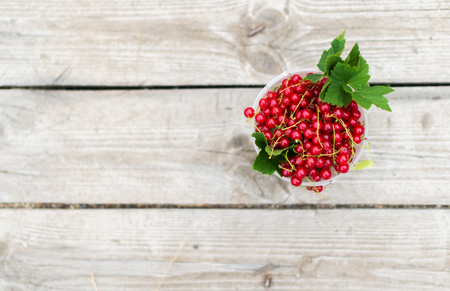 Red currant in a bowl on th wooden background Stock Photo