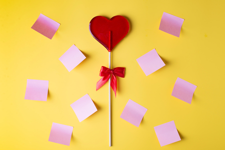 Valentine's day bright yellow background, greeting card concept,  lollipop or sweet candy on sticks with stikers, copy space Archivio Fotografico