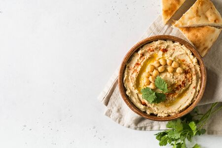 Hummus dip with chickpea, pita  and parsley in wooden plate on white