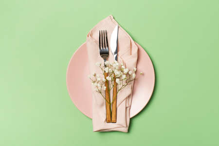 Spring and mothers day table layout with plate and tableware on green background, flat lay, copy space, top view