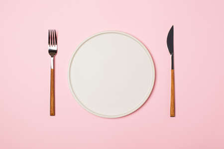 Spring and mothers day table layout with plate and tableware on pink background, flat lay, copy space, top view