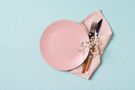 餐具设置与叉子,刀子,餐巾和花在蓝色背景,春天服务,顶视图,副本空间,平躺