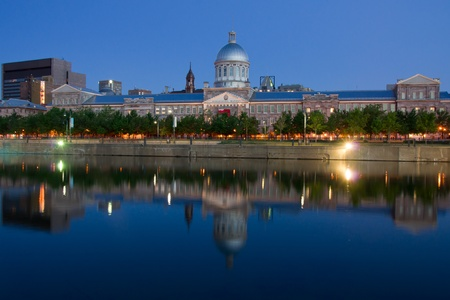 De La Commune street and Bonsecours Market Place in Old Montreal with reflection in the water at dusk Stock Photo
