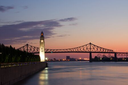 St. Lawrence River with Big Ben in Old Montreal, and Jacques-Cartier Bridge in background, with a beautiful sunrise. Stock Photo