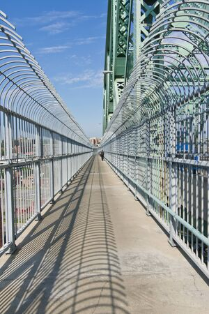 metal structure: Path from the top of a metal structure of a bridge in Montreal, on the west side, and one person went to Montreal for this trail in the background. Stock Photo