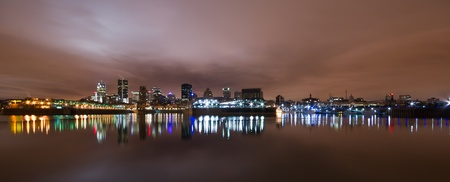 Wide Panoramic View of Montreal at night with color light reflection in water.