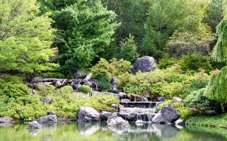 cascade: Small lake  And in the background, a small cascade of water into a large green garden