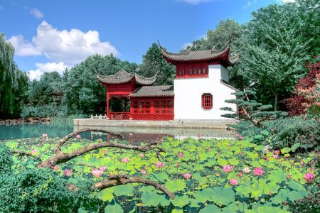 HDR image of a Chinese temple in a garden behind a pool of water photo