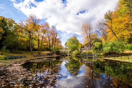 Autumn landscape with reflection of trees in a small lake, and in the background a small bridge with small cascading waterfalls  Stock Photo
