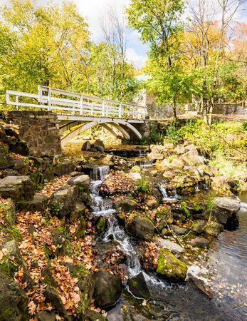 Small footbridge over a small waterfall in autumn landscape