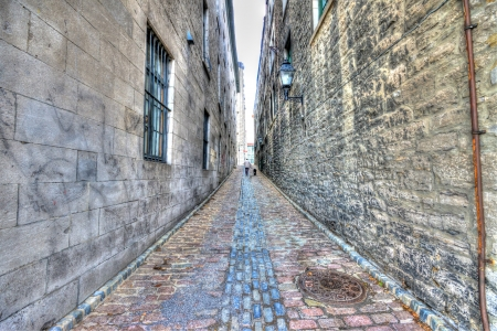 Small narrow street in Old Montreal, and in the background a man walking with his dog, HDR image Stock Photo - 16795289