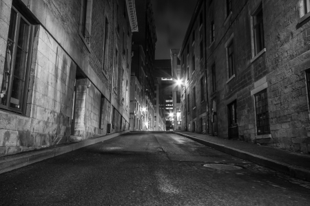 city alley: Deserted narrow street in Old Montreal at night  black and white