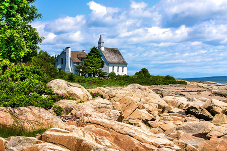 HDR Image Of An Old Abandoned church on the edge of the shore on a beautiful day in Charlevoix, Quebec, Canada photo