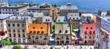 HDR Image Of Old traditional houses in Old Quebec in the summer with tourists and river view