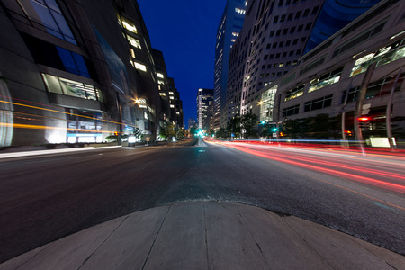 University Street in Montreal with silhouette cars with red rear light and traffic light, with offices buildings background, at dusk   8mm Circular Fisheye Effect  photo