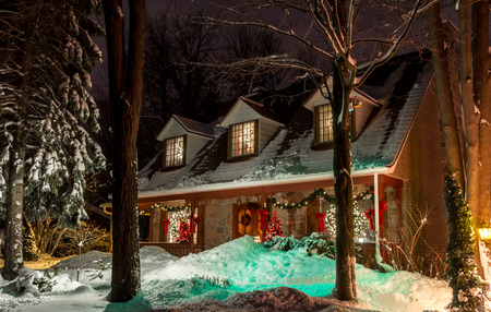 Trees in front of a lighted Christmas Old House