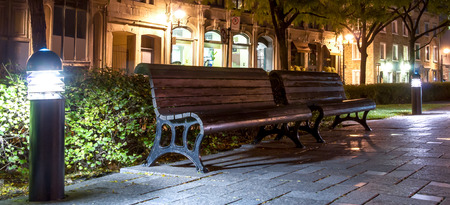 Wooden benches in a pedestrian rest area with floor lamps in Old Montreal at night.