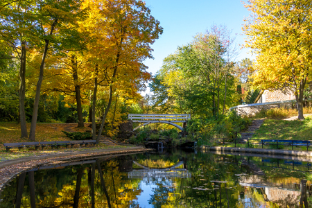 Apart of Small Lake with reflection of trees in water, in a Park in Autumn of Montreal, and little Bridge in Background