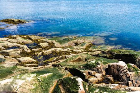 Rock shore and blue water. Stock Photo