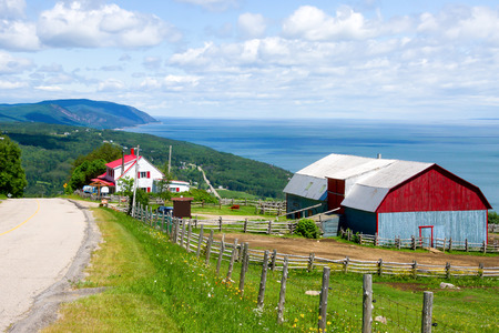 Barn and a house with the red roof on top of the mountain, and in the background a landscape of mountains and sea of Quebec,Canada # 1 Standard-Bild