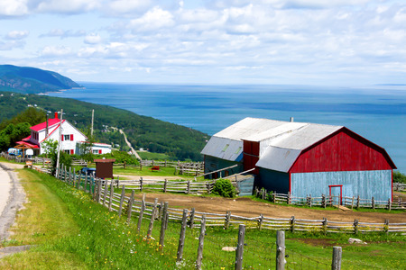 Barn and a house with the red roof on top of the mountain, and in the background a landscape of mountains and sea of Quebec,Canada # 2