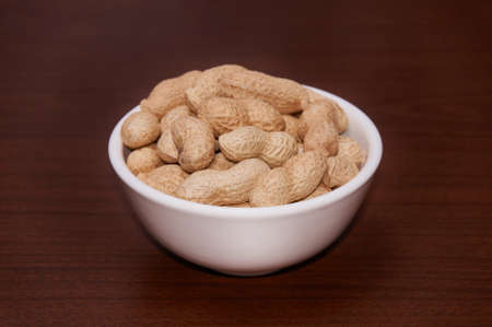 Peanuts are uncleaned against a background of brown wood. Stock Photo