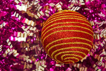 Red Christmas toy with gold stripes on a background close-up. New Year, christmas background.