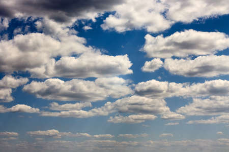 A lot of clouds in the blue sky on a sunny day.