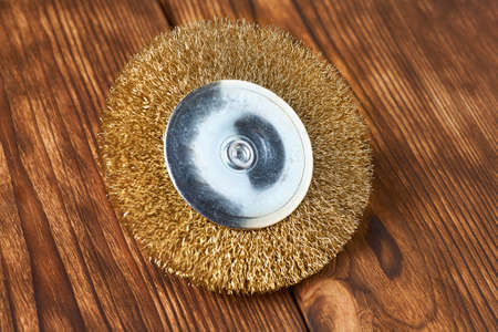 Brass disc for drill machine on wood background