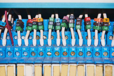 Many intermediate relays installed in a row. They are connected with many wires red with marking. Wires connected to the relay via cable lugs. Markings of different colors with numbers.