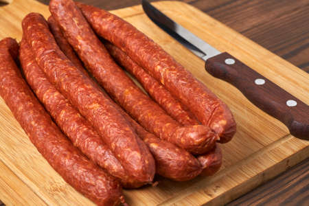 Thin smoked sausage on a wooden background.