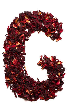 English alphabet. Letter G from dried flowers of hibiscus tea on a white background. Letters for banners, advertisements, menus.