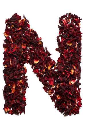 English alphabet. Letter N from dried flowers of hibiscus tea on a white background. Letters for banners, advertisements, menus.