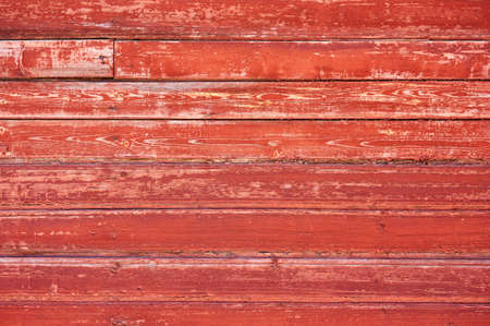 Old wooden background painted with red paint with a texture of cracks and scratches. Red background Stockfoto
